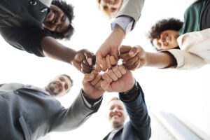 Happy employees join hands for success